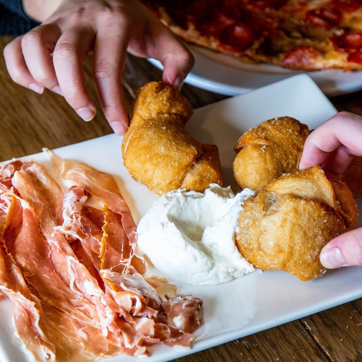 Coccoli - Fried dough rolled in sea salt served with prosciutto and whipped sweet ricotta