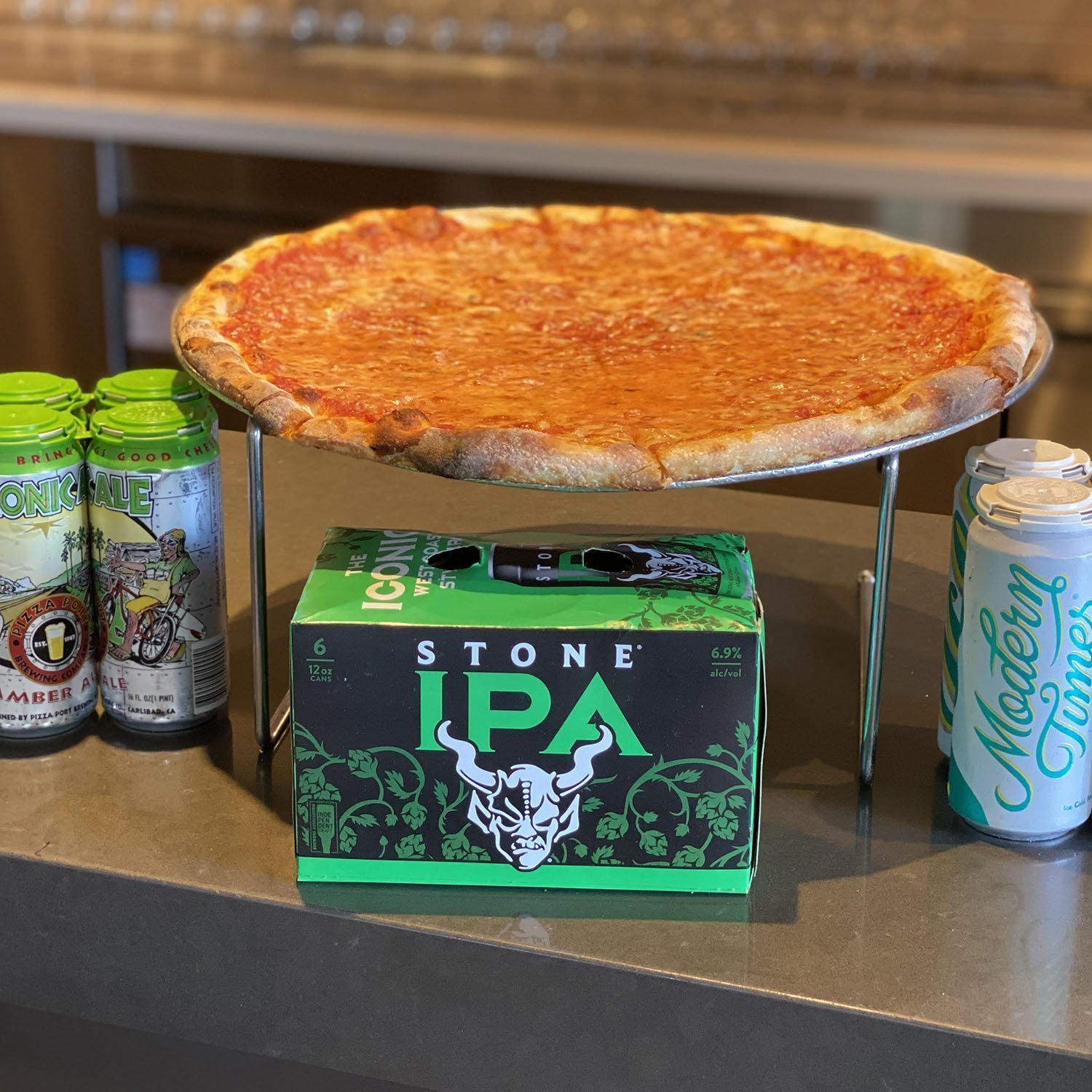A cheese pizza with various canned beer options below